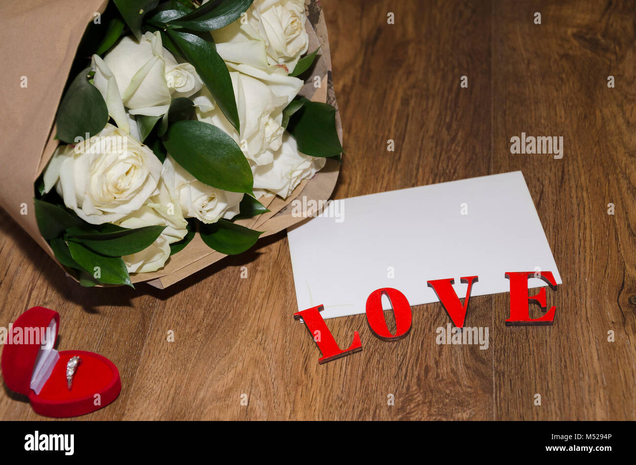 inscription love on a wooden background with a white sheet of paper and a bouquet of white roses in kraft paper Stock Photo