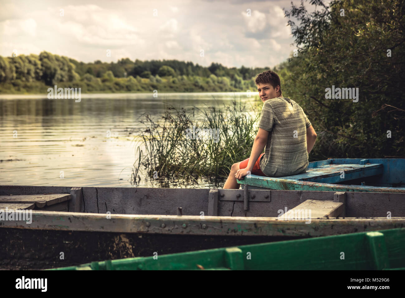Teenager boy lonely contemplation countryside landscape on river bank during countryside summer holidays - Stock Image