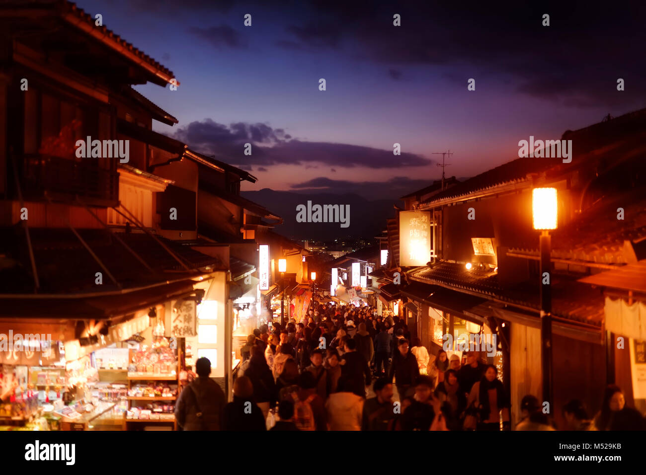 Twilight old Kyoto city scenery at Matsubara dori street in fall with brightly lit shops and street lights, crowded - Stock Image