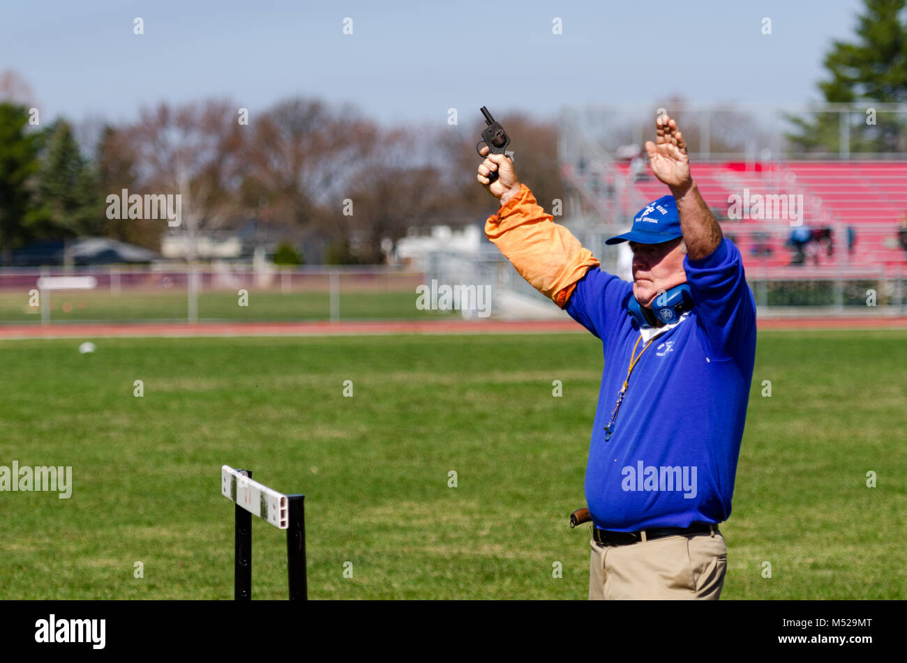 Race official shoots gun to start Track and Field race in Albany, NY.re - Stock Image
