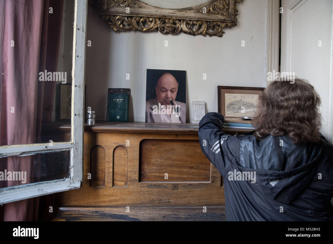 Rubina Tashjian, the widow of the last owner of Aleppo's Baron Hotel, tidies pictures next to a photo of her - Stock Image