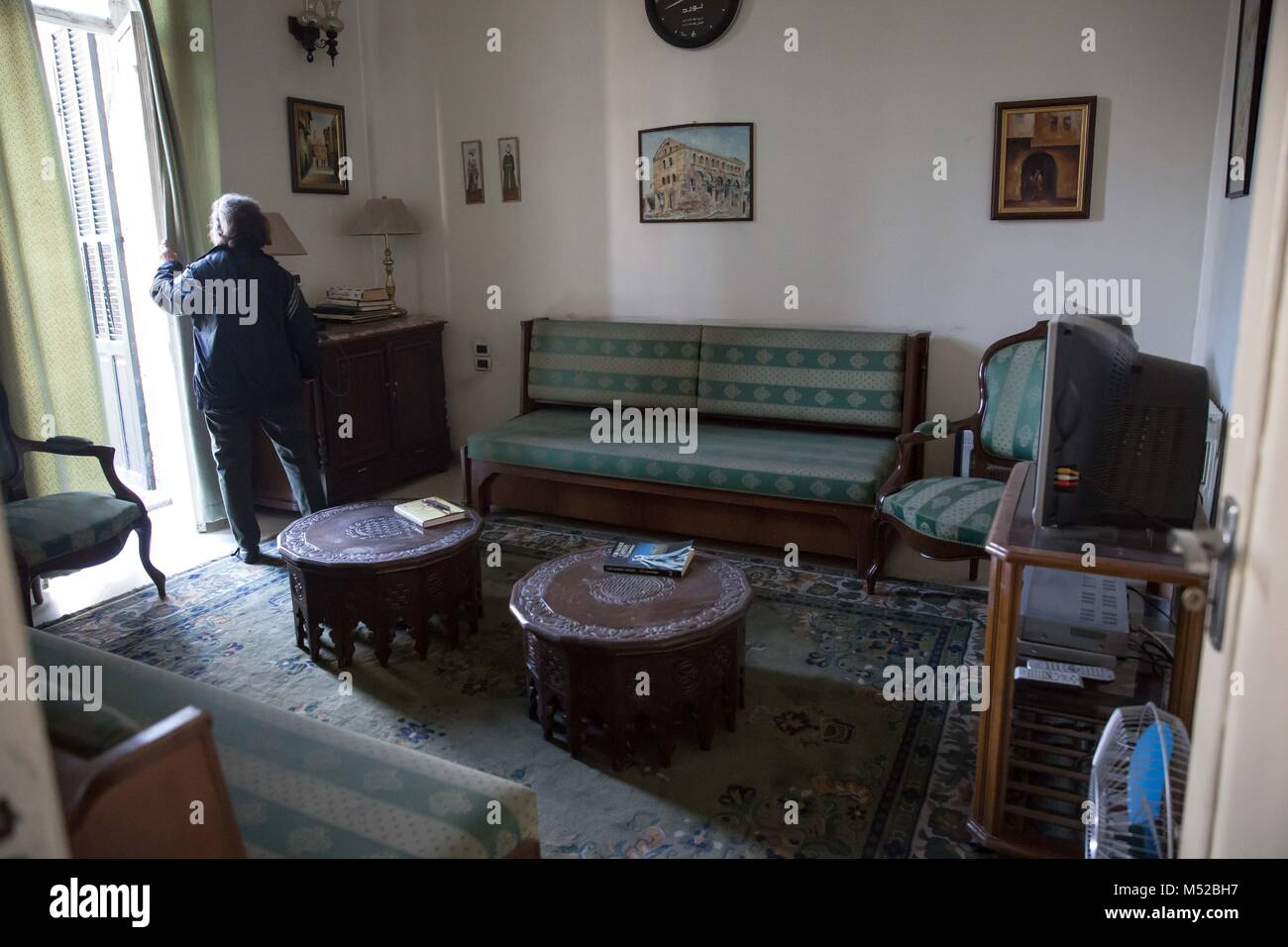 Rubina Tashjian, the widow of the last owner of Aleppo's Baron Hotel, opens the curtains in the presidential - Stock Image