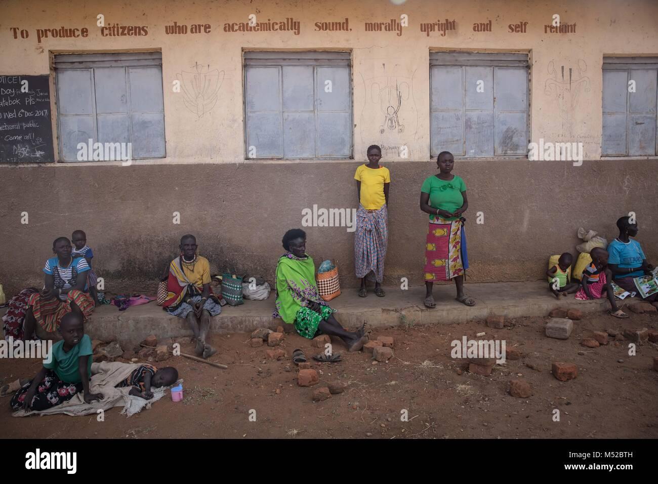 Women and girls sit outside Katabok Primary School. Female genital mutilation (FGM) has been outlawed in Uganda - Stock Image