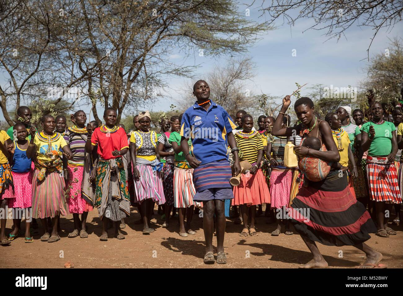 A man and woman from the Pokot tribe dance in front of a line of females close to Katobua village in Karamoja, northern - Stock Image