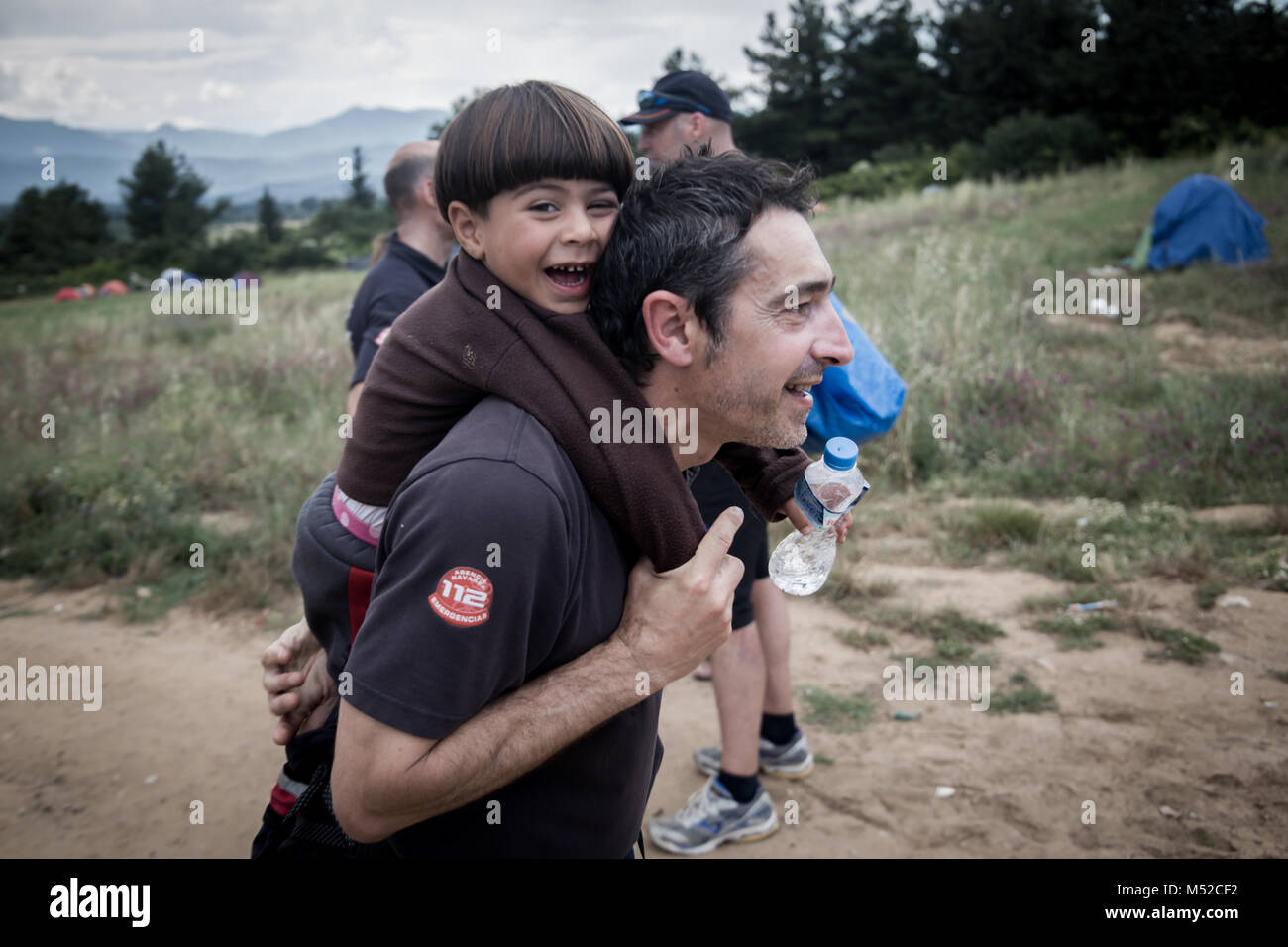 A Spanish volunteer Fireman carrying a Syrian boy at Idomeni refugee Camp in northern Greece. - Stock Image
