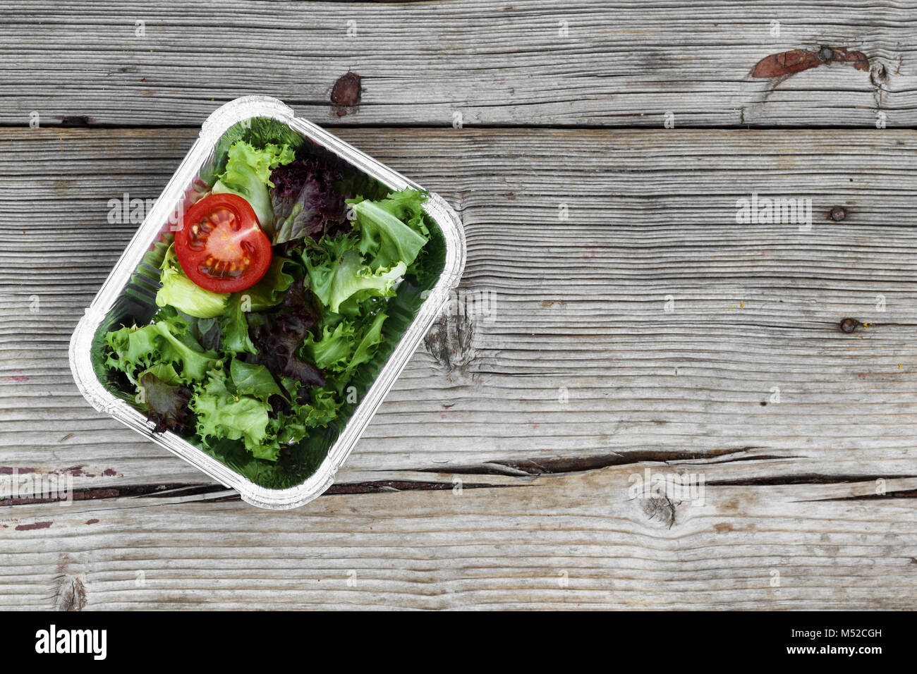 Delicious salad in a container on a wooden table. Close-up. - Stock Image