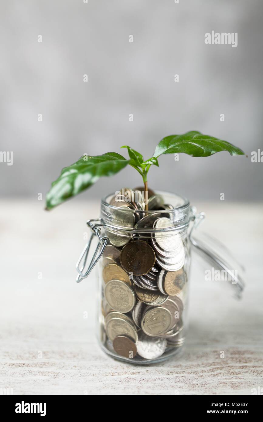Coins in a glass jar - Stock Image