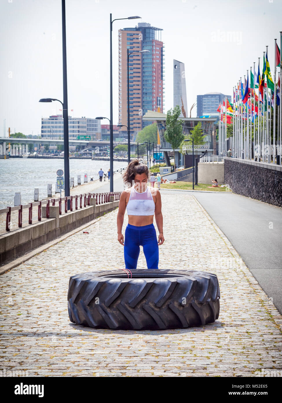 Photo of an attractive young woman working out with a tractor tire in Rotterdam, The Netherlands - Stock Image