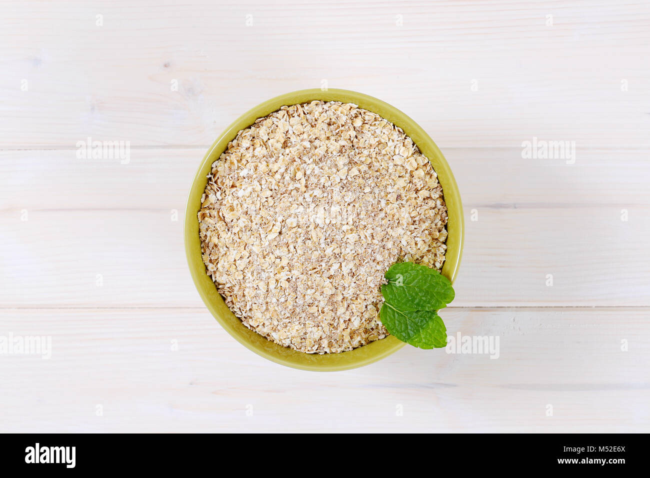 dry rolled oatmeal in a green bowl Stock Photo