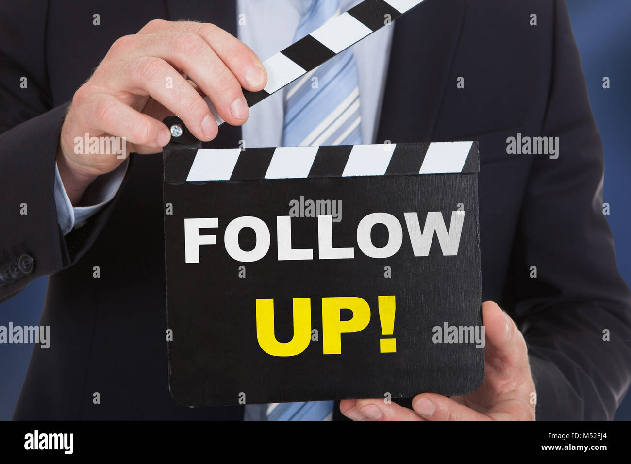 Close-up Of Man Holding Clapboard With Follow Up Text - Stock Image