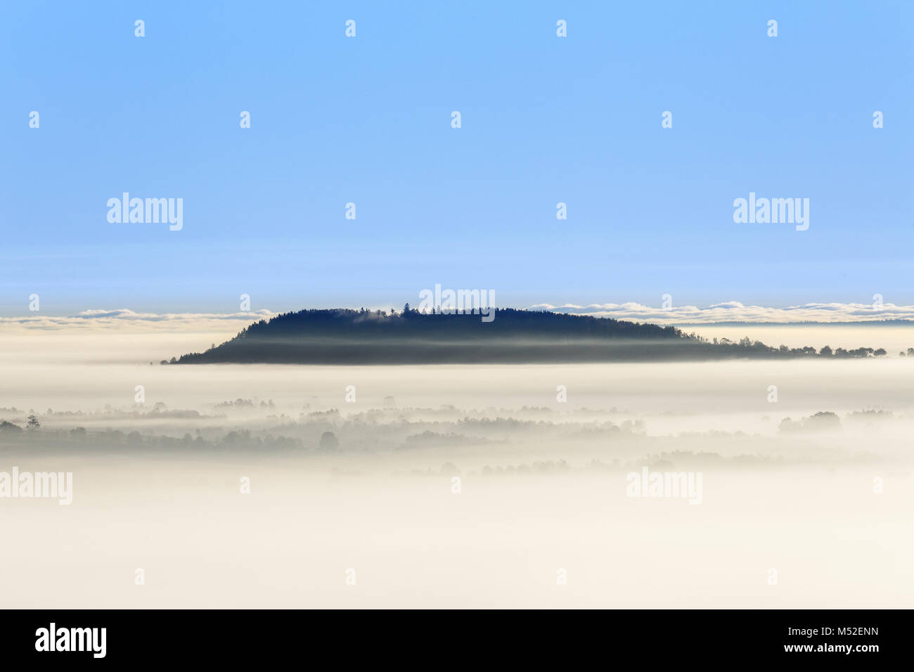 Foggy morning view with a mountain above the fog Stock Photo