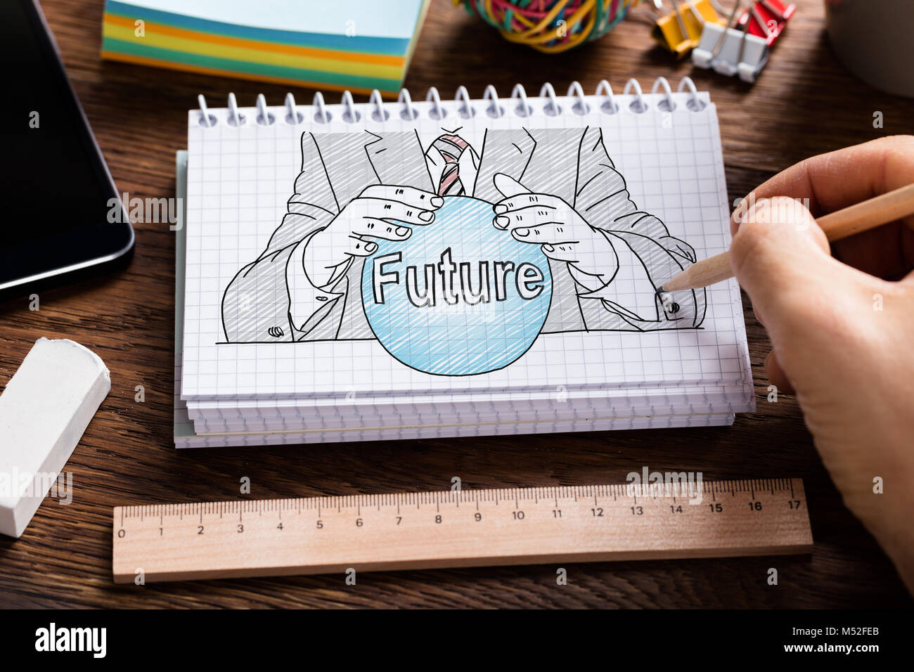 Businessperson's Hand Holding Pencil Drawing Fortune Teller Concept In Spiral Notebook With Stationery - Stock Image