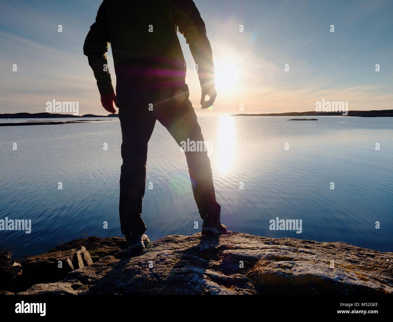 Silhouette of man in outdoor clothes on rocky cliff above sea. Hikerthinking  during sunset in the background. Traveling - Stock Image
