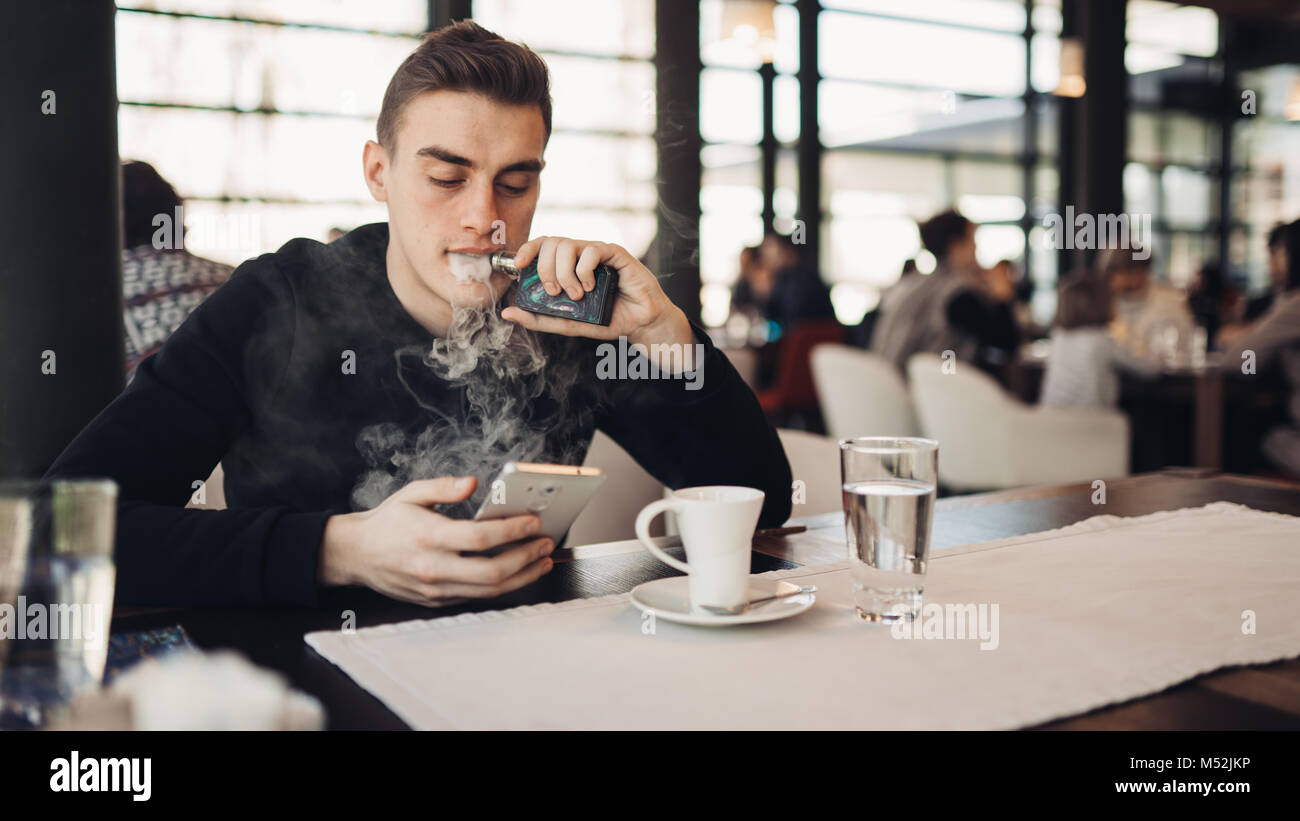 Young man using electronic cigarette to smoke in closed public space.Satisfied e- cigarette user in cafe.Smoking - Stock Image