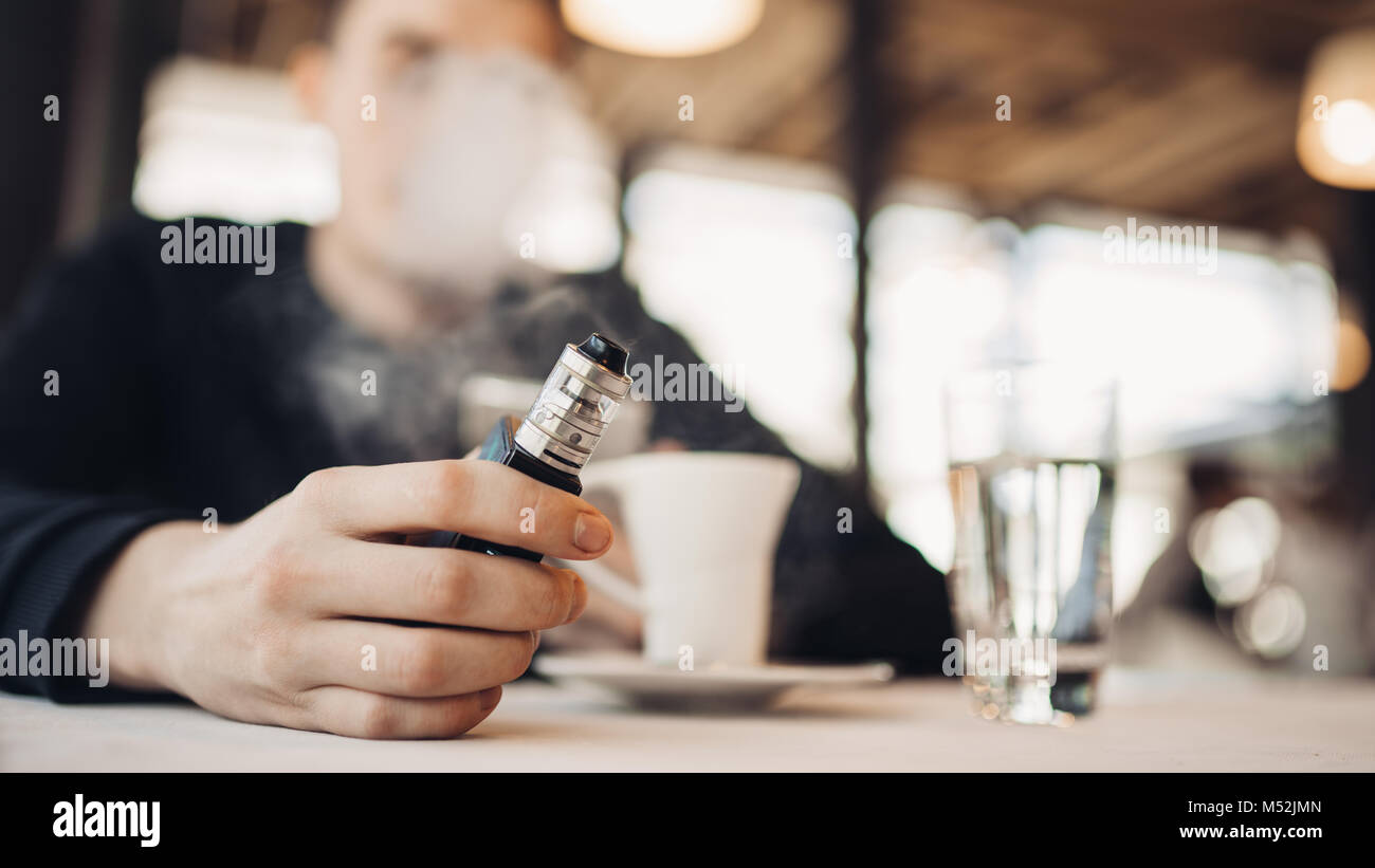 Using electronic cigarette to smoke in public places.Smoke restriction,smoking ban.Using vaping device with flavoured - Stock Image