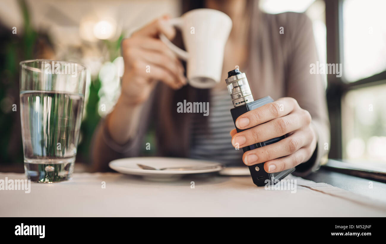 Young woman using electronic cigarette to smoke in public places.Smoke restriction,smoking ban.Using vaping device - Stock Image