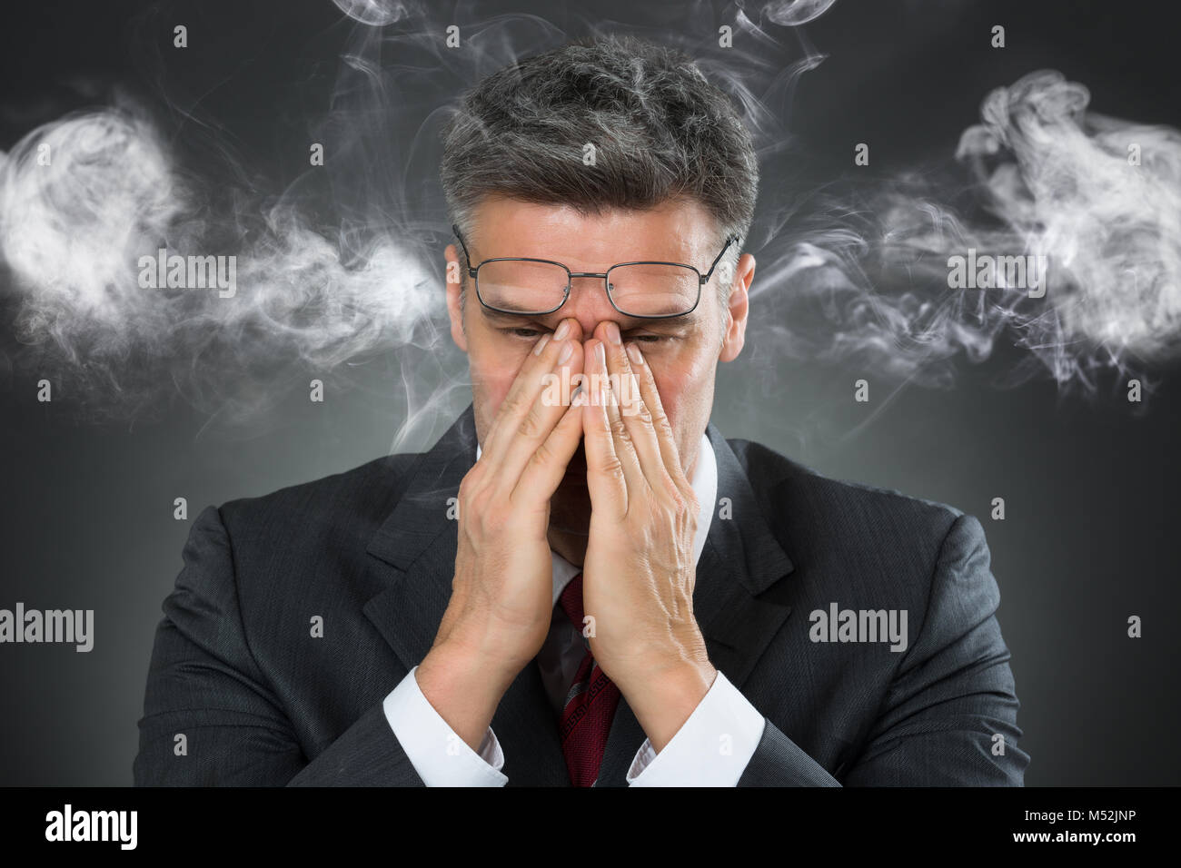 Portrait Of Businessman Covering Mouth From Smoke Over Black Background - Stock Image