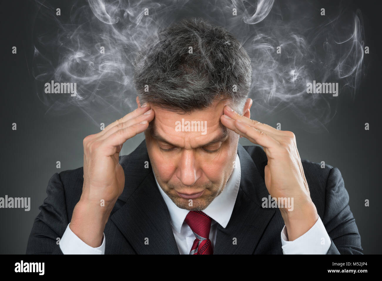 Portrait Of Mature Businessman Suffering From Headache - Stock Image