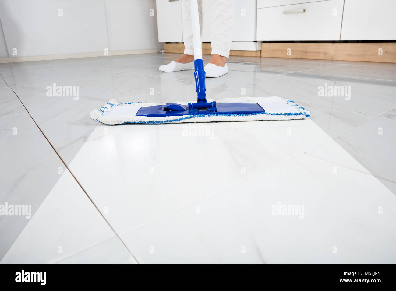 Low section of person wiping floor with mop in kitchen room stock