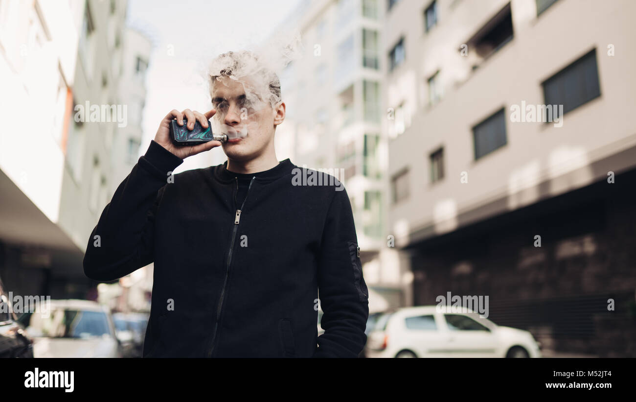 Young man using electronic cigarette to smoke in public places.Smoke restriction,smoking ban.Using vaping device - Stock Image