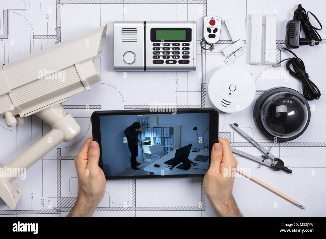 Person looking at office security camera on mobile phone with stock person looking at office security camera on mobile phone with security equipments on blueprint document malvernweather Gallery