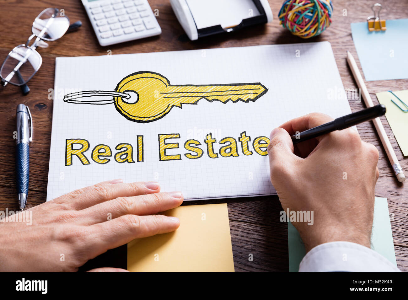 Close-up Of Person's Hand Drawing Real Estate Key On Paper - Stock Image