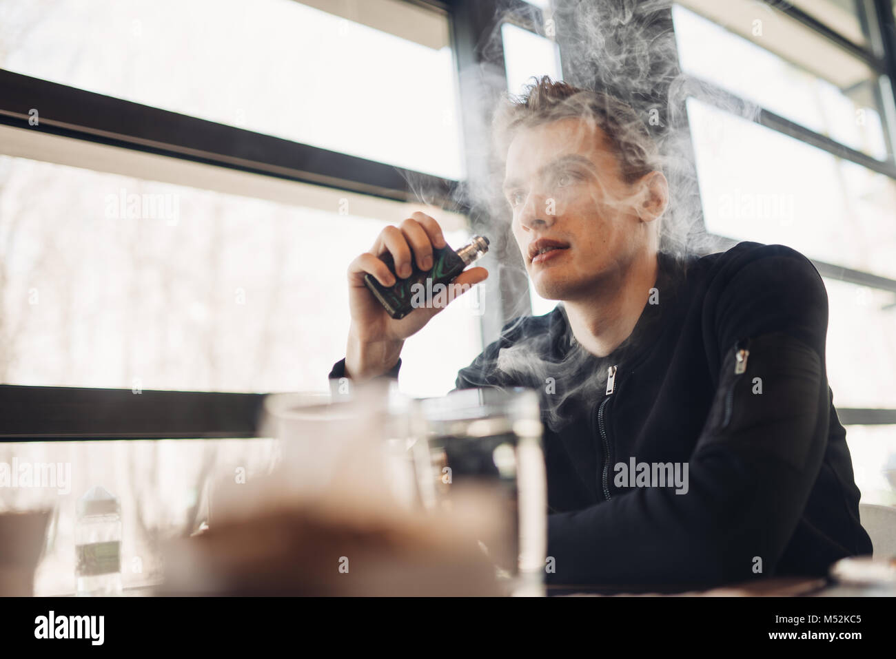 Young man vaping in closed public space.Smoking electronic cigarette in cafe.Nicotine addiction.Way to quit smoking,old - Stock Image