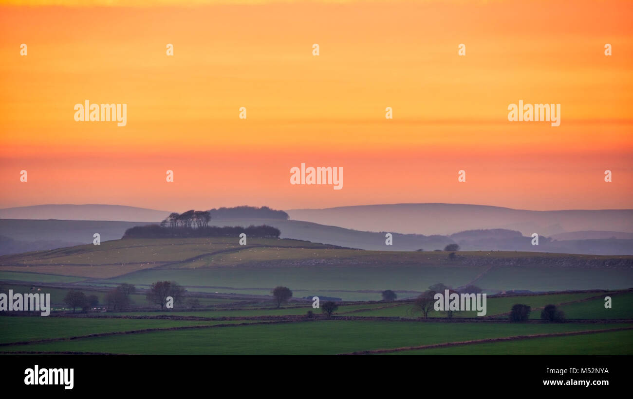 Sunset over Minning Low hill Historic England monument with a chambered tomb & two bowl barrows viewed from Harborough Stock Photo