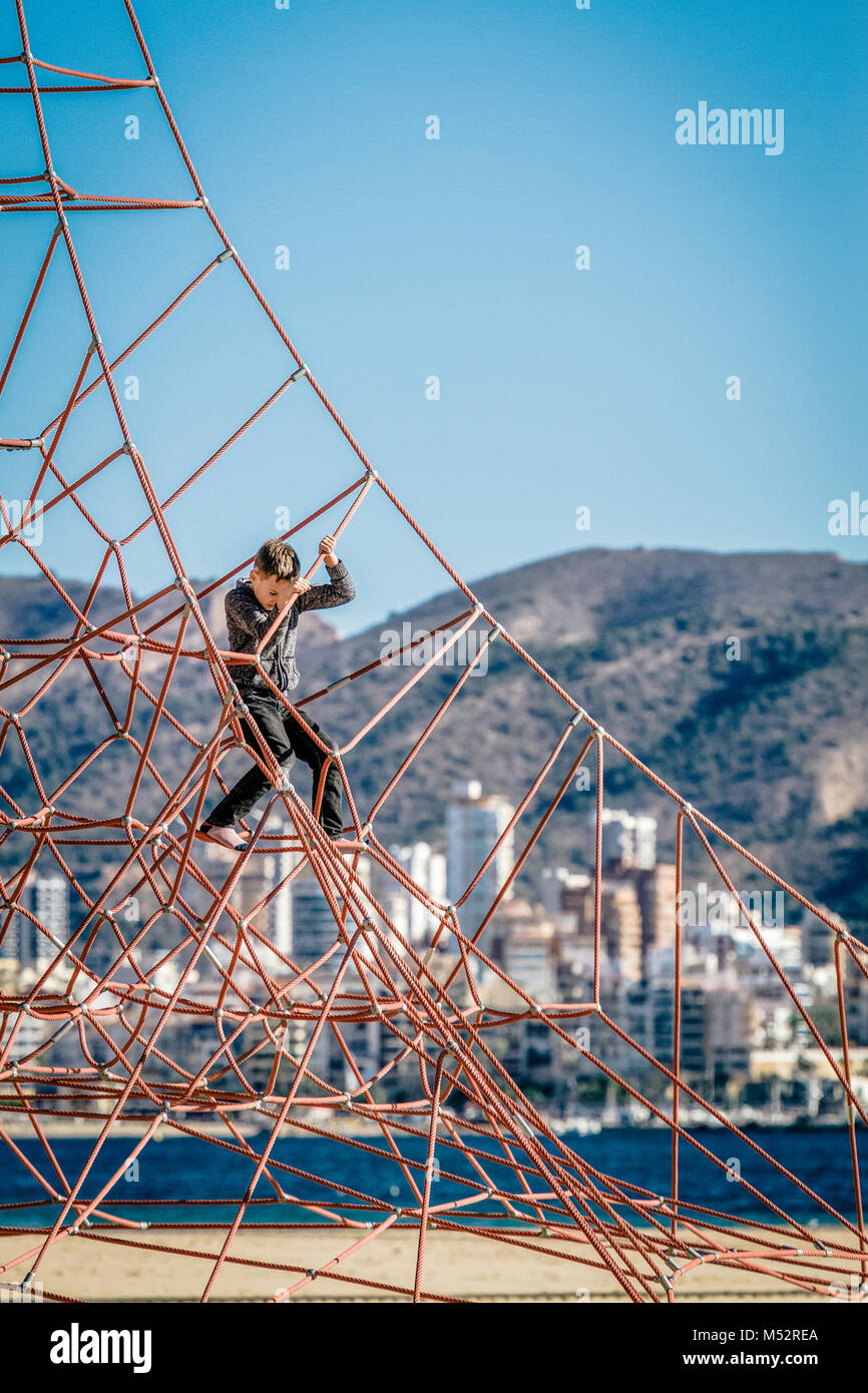 Little boy climbing on the rope at playground in Benidorm beach - Stock Image