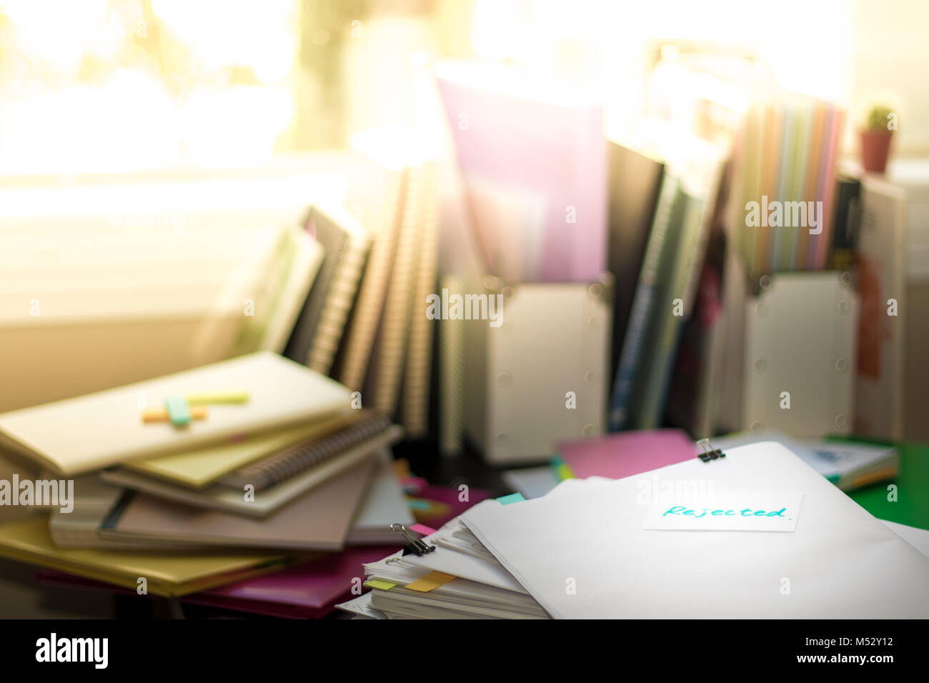 Rejected; Stack of Documents. Working or Studying at messy desk. - Stock Image