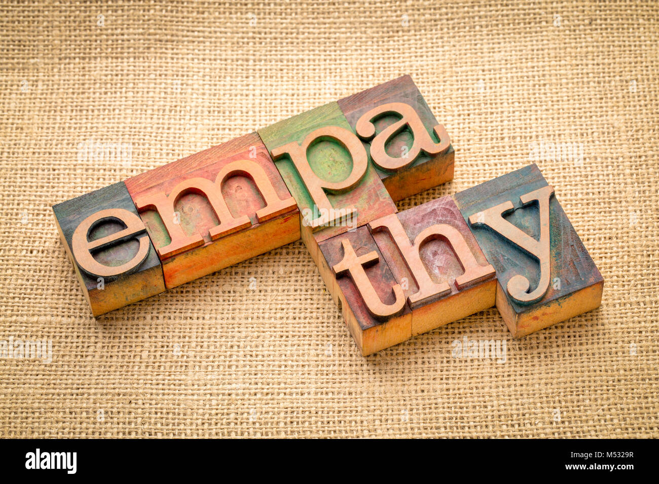 empathy word abstract in letterpress wood type against burlap canvas - Stock Image