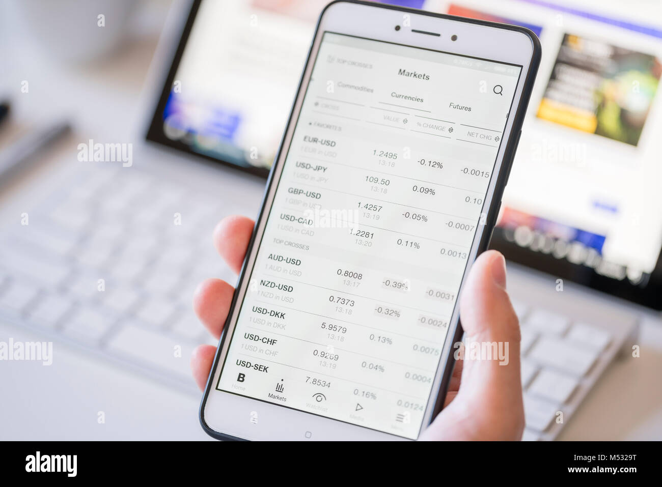 Checking currency exchange rates on a smartphone - Stock Image