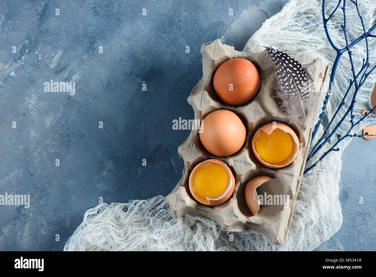 Easter decorations concept with fresh eggs in a carton, tree branches and cloth runner on a concrete background. - Stock Image
