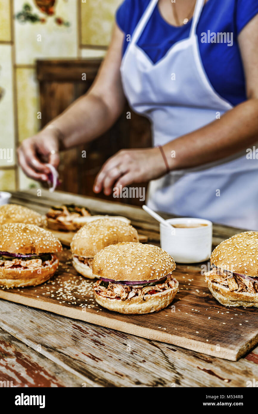 Home cooking. A woman is cooking burgers - Stock Image