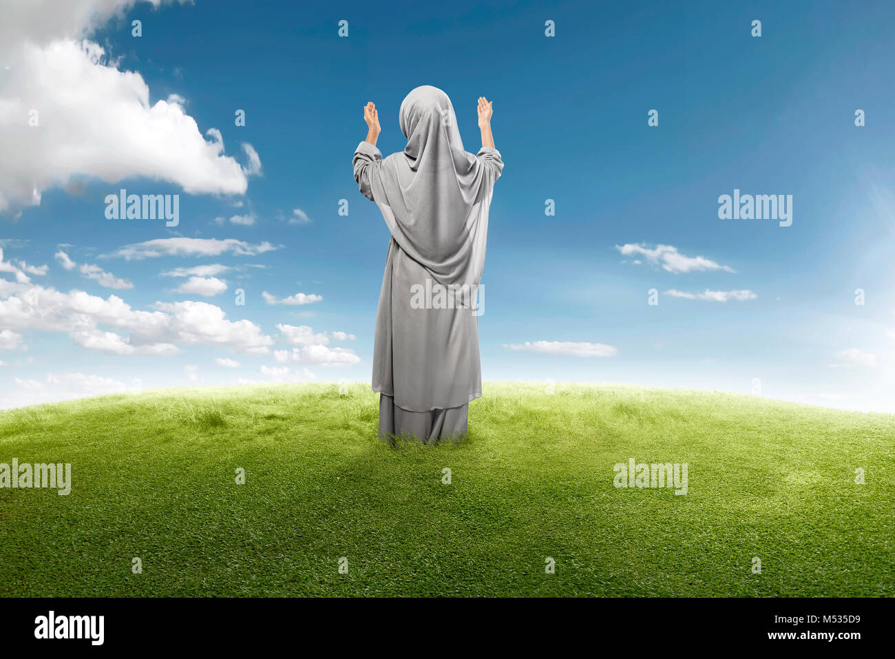 Back view of asian muslim girl praying to god on green meadow stock image
