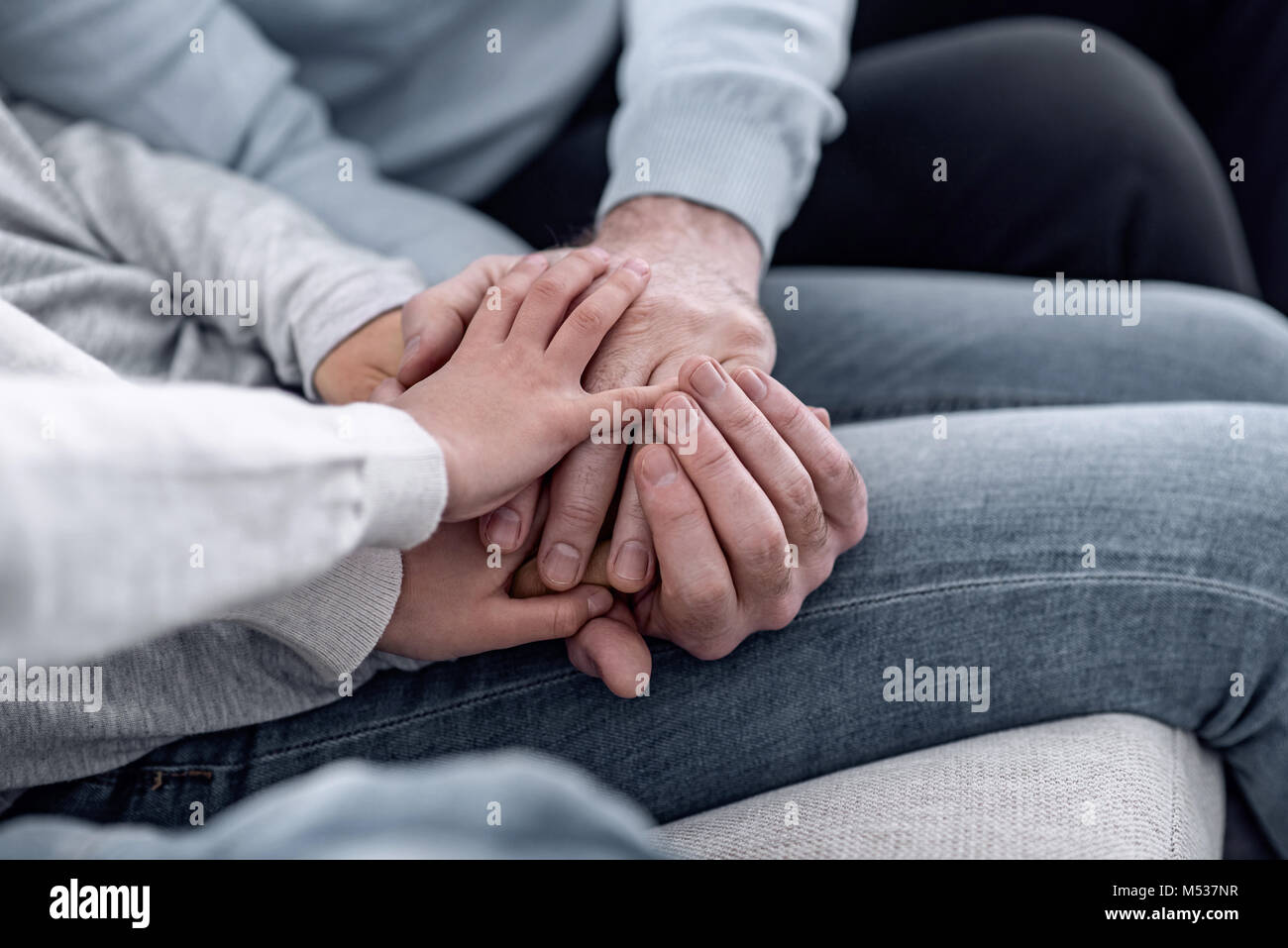 Little boy putting his hand on the hands of his parents - Stock Image