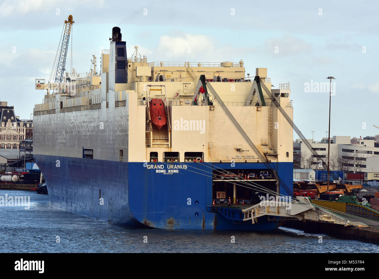 A modern car transporter vessel or large ship alongside the docks at the port of Southampton being loaded with the - Stock Image