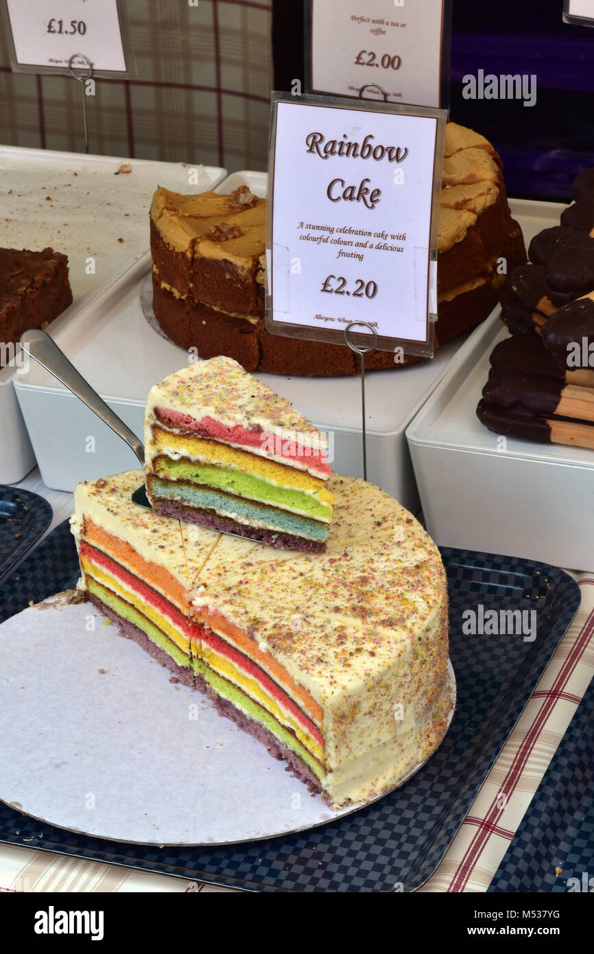 A brightly coloured baking rainbow cake slices for sale on a market stall selling delicacies and sweet cakes and - Stock Image