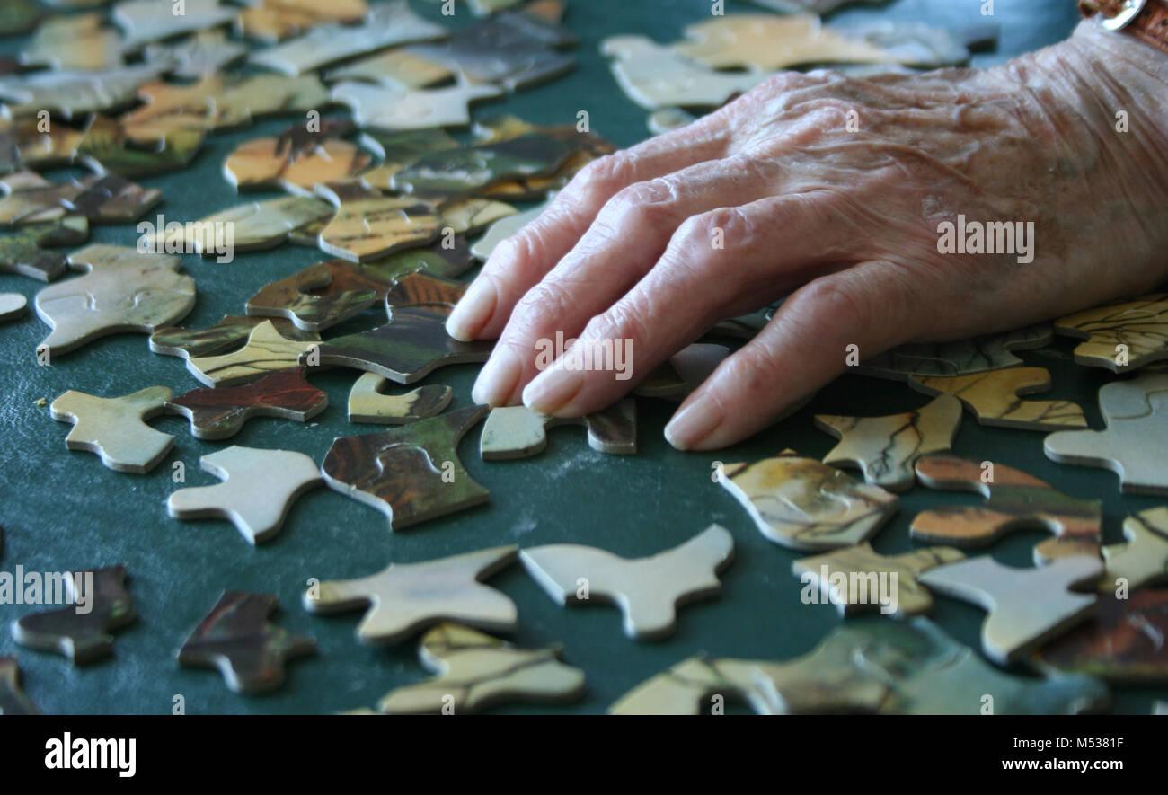 Senior with Arthritis Building Puzzle - Stock Image