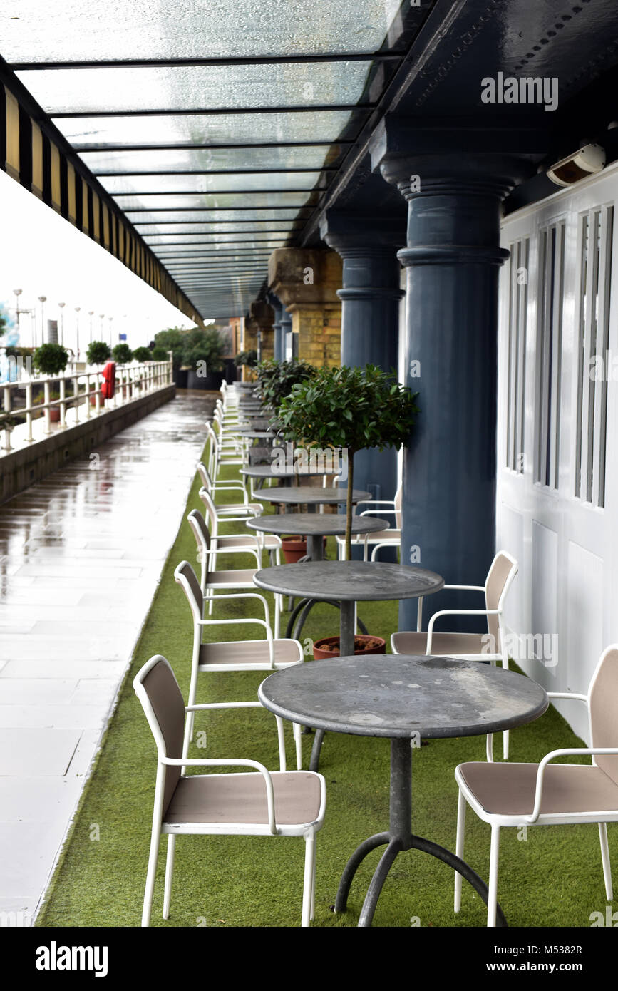 A row or line of tables and chairs on the riverbank of the thames in central london outside of a restaurant or cafe - Stock Image