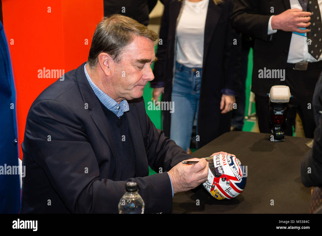 Nigel Mansell signing autographs for fans at The London Classic Car Show & Historic Motorsport International - Stock Image