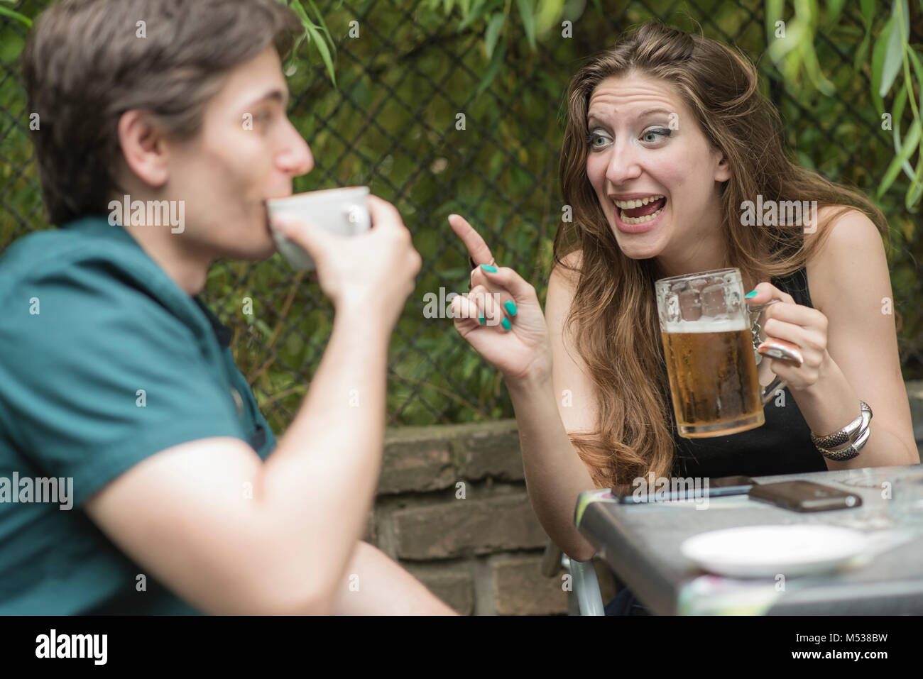 Date going well, man and woman chatting over drinks - Stock Image