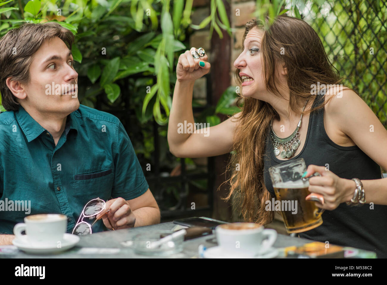 Angry girlfriend about to punch her boyfriend - Stock Image