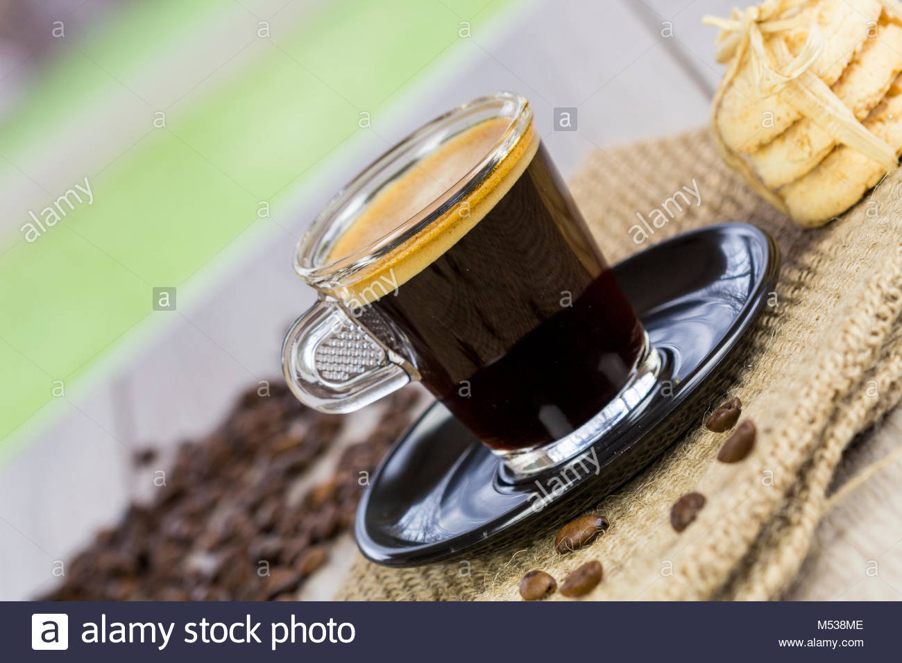 Strong mug of freshly brewed espresso coffee with coffee beans with a dainty pile of crunchy cookies tied together Stock Photo