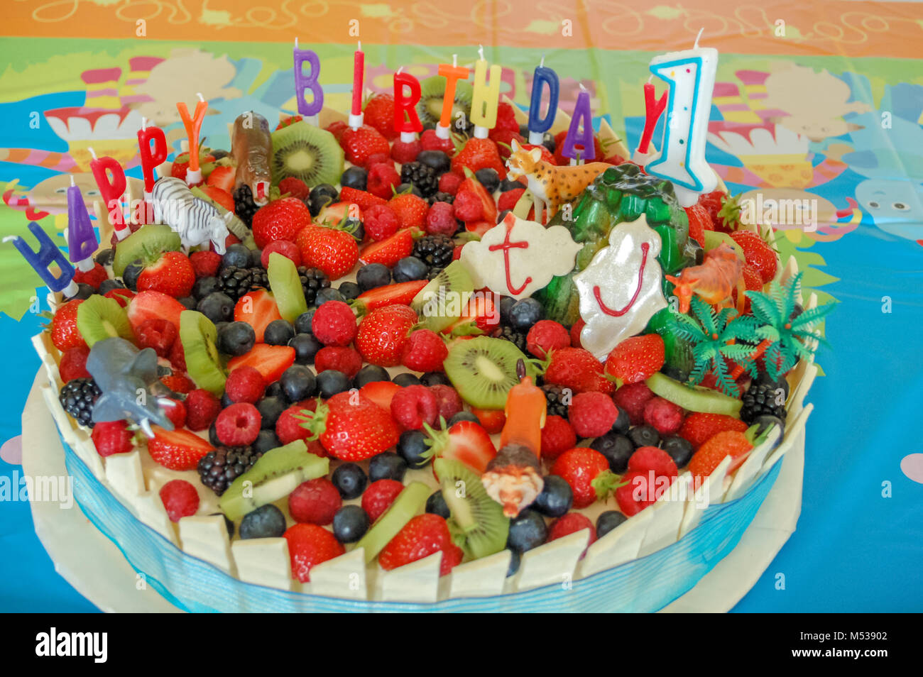 A First Birthday Cake Decorated With Summer Fruits Toy Animals And Candles