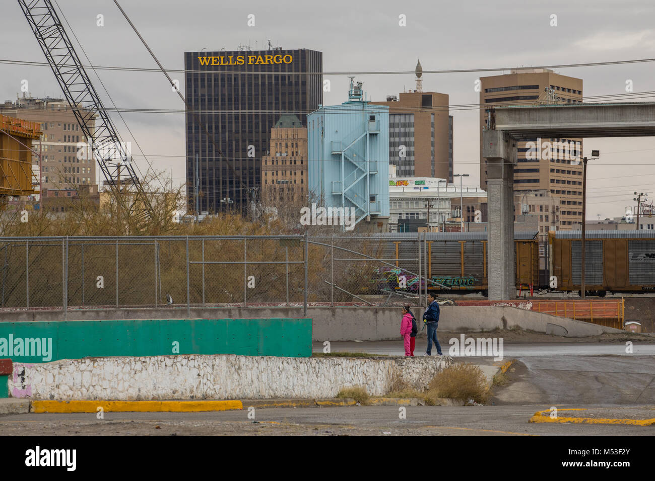 A mother and child walk through a Juarez colonia on the US-Mexico border, with skyscrapers of downtown El Paso in - Stock Image