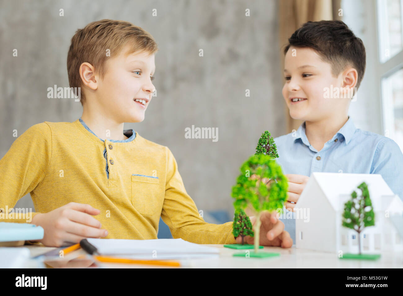 Cheerful pre-teen boys discussing their ecology project - Stock Image