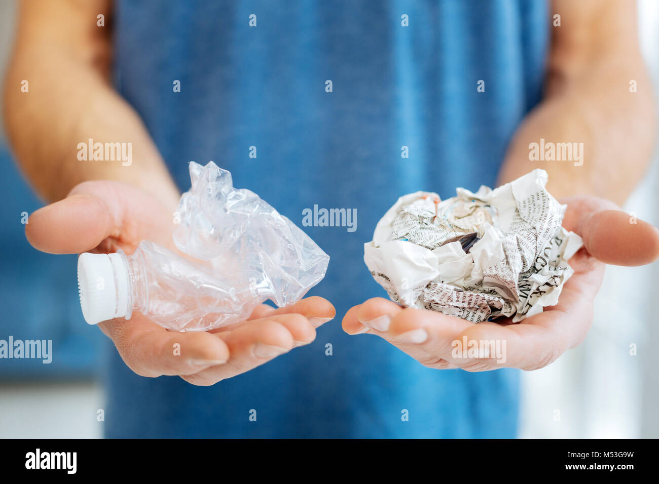 Young man posing with plastic bottle and crumpled newspaper - Stock Image