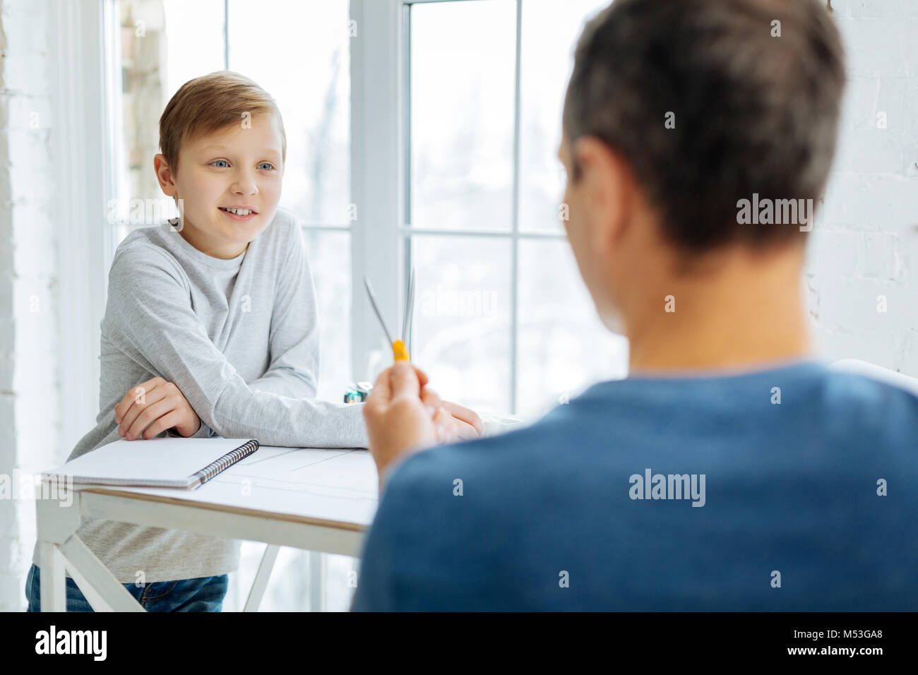 Pre-teen boy learning how to use compass from father - Stock Image