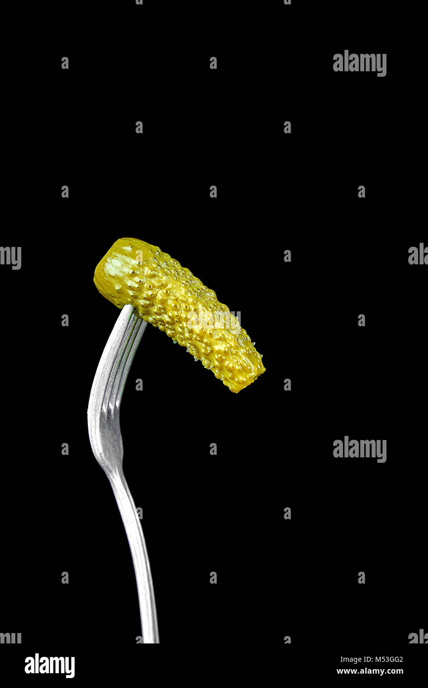 Fork with pickled cucumber on black background. Copy space. - Stock Image